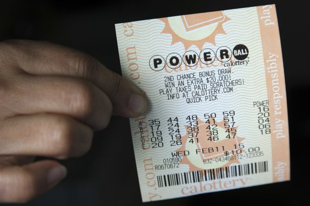 A woman holds a ticket purchased for the U.S.  Powerball lottery on February 9, 2015. (Reuters)