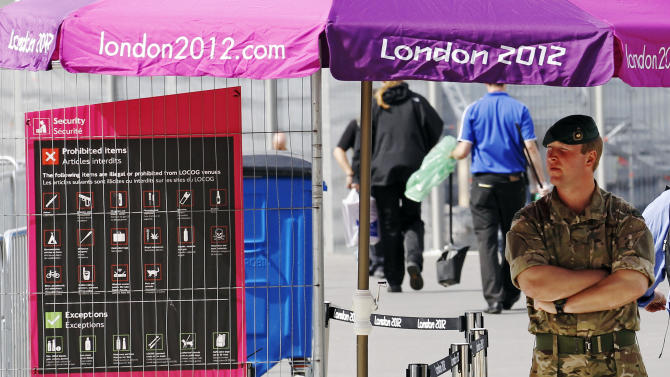 A soldier mans a security check point at an entrance to the London 2012 Olympic Park at Stratford in London