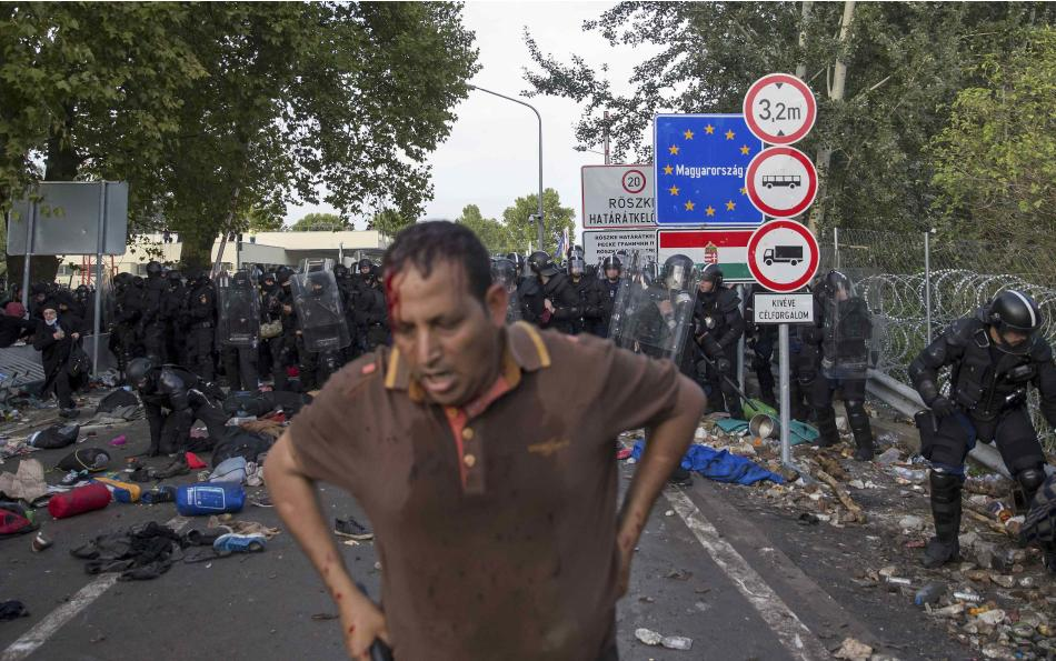 A migrant stands after clashing with Hungarian riot police at the border crossing with Serbia in Roszke