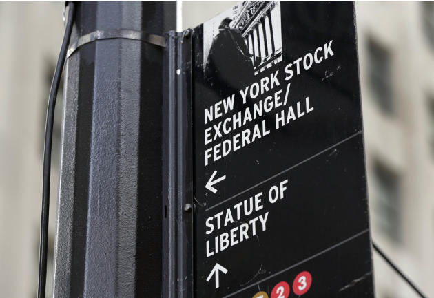 FILE - In this Oct. 2, 2014, file photo, a street sign directs people to The New York Stock Exchange, Federal Hall, and the Statue of Liberty, in New York's Financial District. Chinese stocks fell