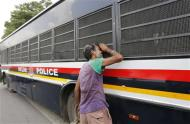 A man peeks into the police vehicle carrying four men, who were found guilty of the fatal gang-rape of a young woman on a bus in New Delhi, as the bus leaves a court in New Delhi September 10, 2013. REUTERS/Adnan Abidi