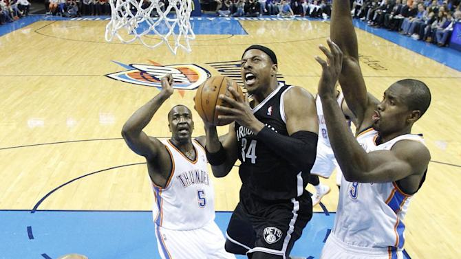 CORRECTS WINNING TEAM - Brooklyn Nets forward Paul Pierce (34) shoots between Oklahoma City Thunder guard Derek Fisher (6), center, Kendrick Perkins (5) and forward Serge Ibaka (9) in the third quarter of an NBA basketball game in Oklahoma City, Thursday, Jan. 2, 2014. Brooklyn won 95-93