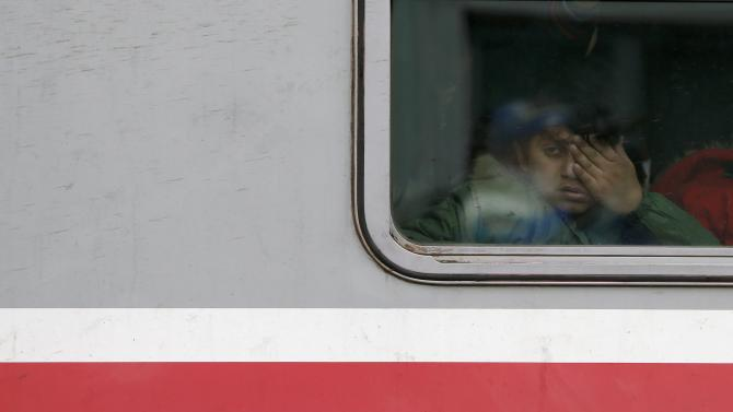 Migrant child looks through of a train window at a train station in the town of Sid