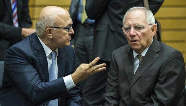 French Finance Minister Michel Sapin (L) gestures as he speaks with German Finance Minister Wolfgang Schaeuble during a meeting of the Eurogroup finance ministers in Brussels on July 12, 2015