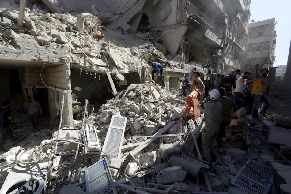 Residents and Civil Defence members look for survivors at a damaged site after what activists said was a barrel bomb dropped by forces loyal to Syria's President Bashar al-Assad and hit a school a