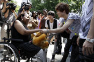 Donika Sterling from New York, left, shakes hand with Tae Min, her most favorite member of South Korean pop group SHINee after their meeting in Seoul, South Korea, Wednesday, June 20, 2012. The 15 year-old American K-pop fan, who is suffering a disease that gradually causes loss of muscle tissue and slows down parts of the body, met and sang with the boy band she idolizes. (AP Photo/Lee Jin-man)