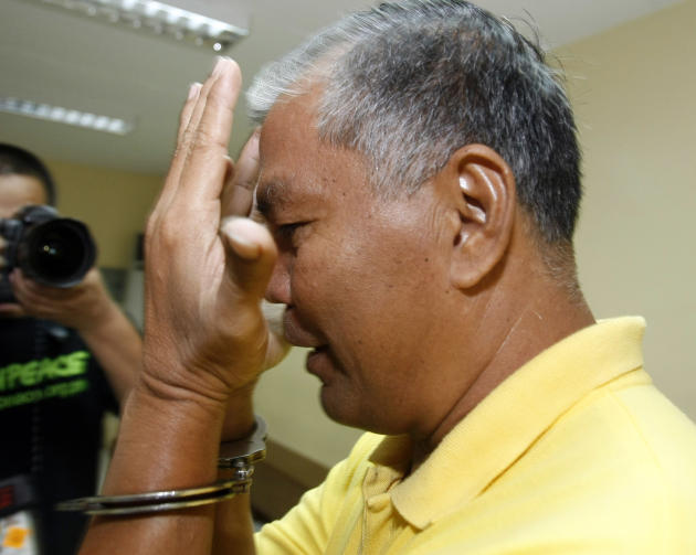 A handcuffed suspect in the massacre of 57 people, including 32 journalists and staff, in Maguindanao province in southern Philippines, tries to shield his face from the media as he attends the contin