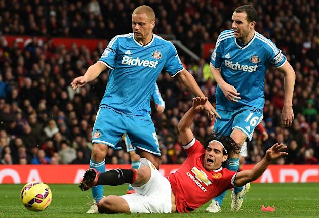 Manchester United's Radamel Falcao (front) falls after a foul by Sunderland's Wes Brown (L) and John O'Shea (R) for a penalty during their English Premier League football match in Manchest