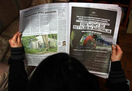 A woman reads a newspaper containing an advertisement (R) publicising the Australian government's new policy on asylum seekers arriving by boat, in Sydney August 2, 2013. REUTERS/David Gray