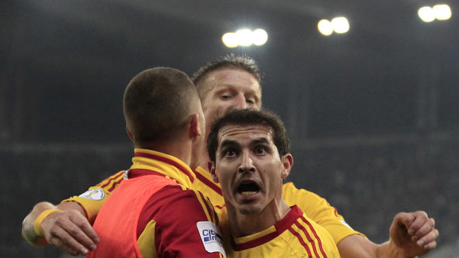 Romania's Bogdan Sorin Stancu, front,  celebrates after scoring against Greece during their World Cup qualifying playoff first leg soccer match at the Karaiskaki stadium in the port of Piraeus, near Athens, Friday, Nov. 15, 2013
