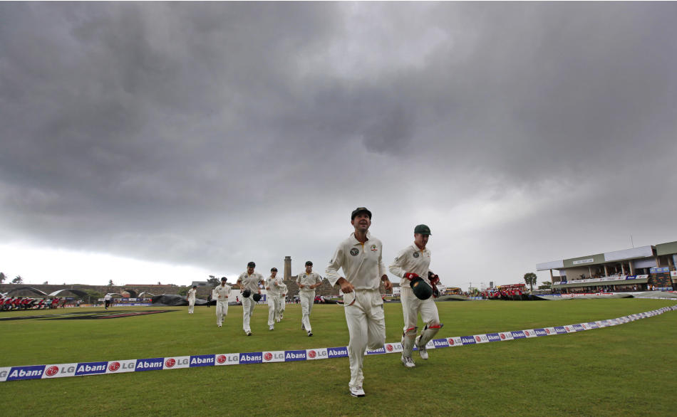 Australia's Ricky Ponting, second right, leads the team back to pavilion after umpires call off the play as dark clouds gather during the fourth day of their first test cricket match against Sri Lanka