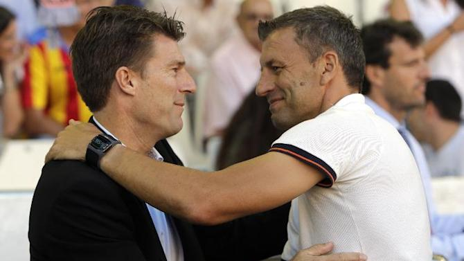 Swansea City's manager Michael Laudrup from Denmark greets Valencia's coach Miroslav Djukic from Serbia before their Europa  League Group A soccer match against Valencia  at the Mestalla stadium in Valencia, Spain, Thursday , Sept. 19, 2013