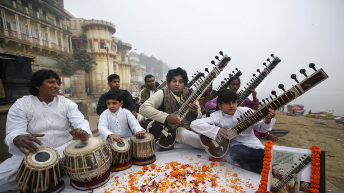 Members of Vande Mataram music society play sitars during a function to offer tributes to legendary Indian sitar player Ravi Shankar on the banks of  the Ganges River in Varanas , India, Thursday, Dec. 13, 2012. Shankar, who is credited with connecting the world to Indian music, died Tuesday in San Diego at the age of 92. (AP Photo/Rajesh Kumar Singh)