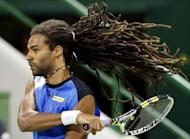 Germany's Dustin Brown returns the ball to Spain's David Ferrer during the 2013 ATP Qatar Open in Doha on January 1, 2013. Ferrer won 5-7, 6-3, 6-2