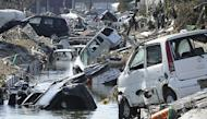 Vehicles block a canal after they were deposited there in Tagajo in Miyagi prefecture. Japan raced to avert a meltdown of two reactors at a quake-hit nuclear plant Monday as the death toll from the disaster on the ravaged northeast coast was forecast to exceed 10,000