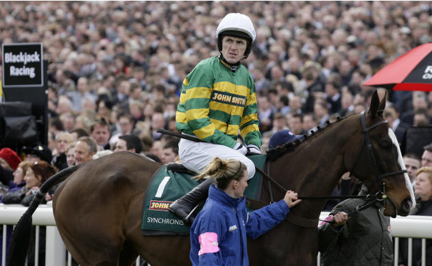 Syncronised with jockey Tony McCoy is led to the start of the Grand National horse race at Aintree Racecourse Liverpool, England, Saturday, April 14, 2012. Synchronised, who won the Cheltenham Gold Cu