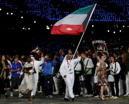 Kuwait's flag bearer Fehaid Aldeehani holds the national flag as he leads the contingent in the athletes parade during the opening ceremony of the London 2012 Olympic Games at the Olympic Stadiu