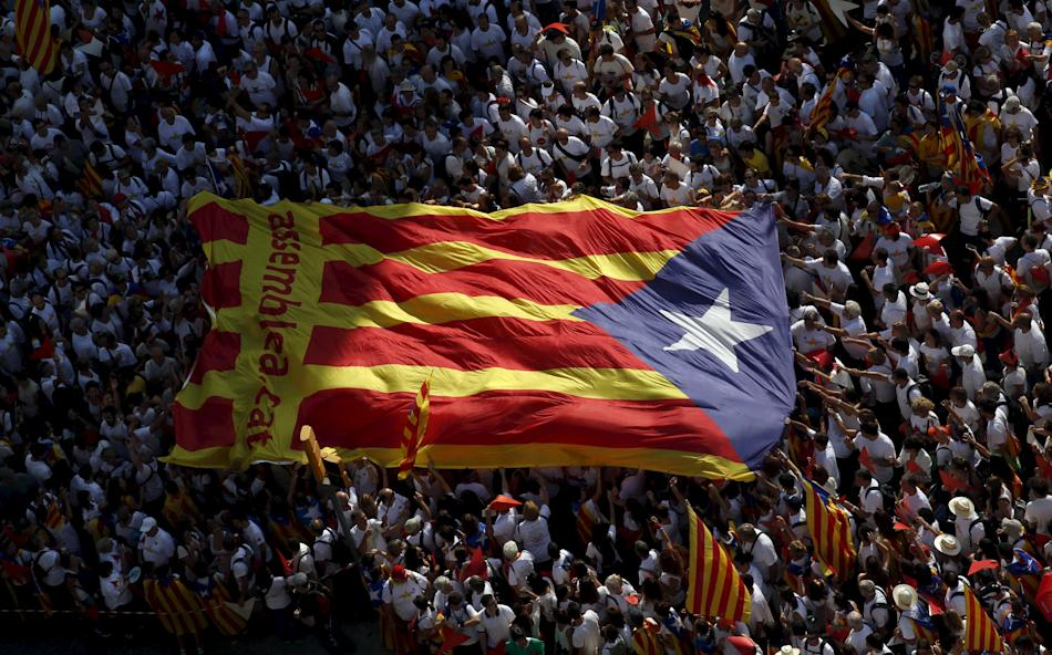 Catalan pro-independence supporters hold a giant Catalan separatist flag during a demonstration called