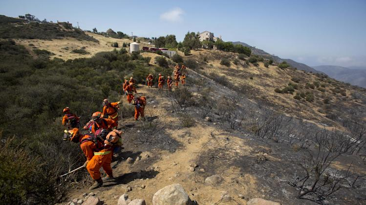 Crews work on the fire line after a wildfire near Point Mugu, Calif., Saturday, May 4, 2013. High winds and withering hot, dry air was replaced by the normal flow of damp air off the Pacific, significantly reducing fire activity.  (AP Photo/Ringo H.W. Chiu)