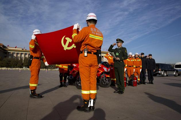 Chinese paramilitary firefighters take a pledge of allegiance in front of a Chinese Communist Party flag on Tiananmen Square in Beijing, Wednesday, March 4, 2015. China's military budget will grow