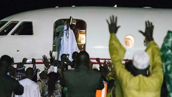 Gambia's former president Yayha Jammeh (C), the country's leader for 22 years, waves from the plane as he leaves the country in Banjul on January 21, 2017