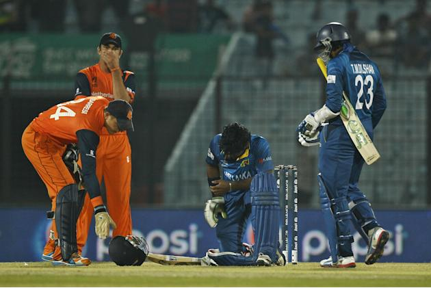 Sri Lanka's Kusal Perera, center, sits after he was hit by a ball during their ICC Twenty20 Cricket World Cup match against Netherlands in Chittagong, Bangladesh, Monday, March 24, 2014. (AP Photo