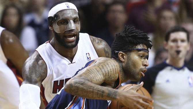 Miami Heat's LeBron James, left, blocks Charlotte Bobcats' Chris Douglas-Robert (55) during the second half of an NBA basketball game in Miami, Monday, March 3, 2014. LeBron James scored a team recond of 61 points. The Heat won 124-107. (AP Photo/J Pat Carter)
