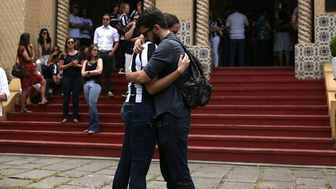 People mourn as coffins carrying three journalists who were victims of the plane crash in Colombia, arrive at the Botafogo club headquarters in Rio de Janeiro