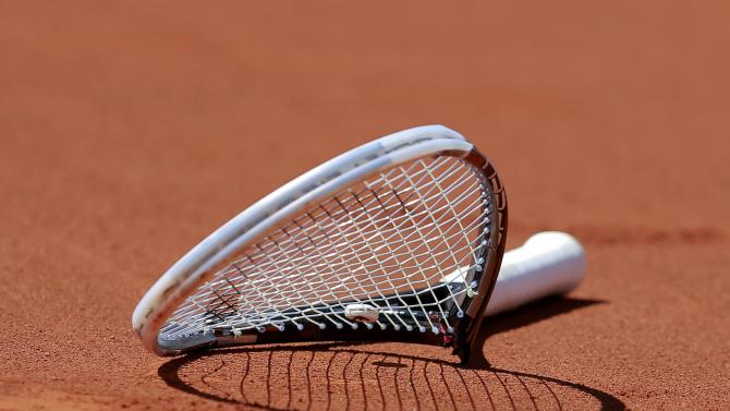 The broken racket of Novak Djokovic of Serbia is seen on the court after he smashed it during his men's semi-final match against Ernests Gulbis of Latvia at the French Open tennis tournament at the Roland Garros stadium in Paris