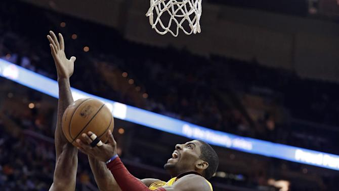 Cleveland Cavaliers' Kyrie Irving, center, jumps to the basket between Los Angeles Clippers' Antawn Jamison, left, and Chris Paul, right, during the fourth quarter of an NBA basketball game on Saturday, Dec. 7, 2013, in Cleveland. The Cavaliers won 88-82