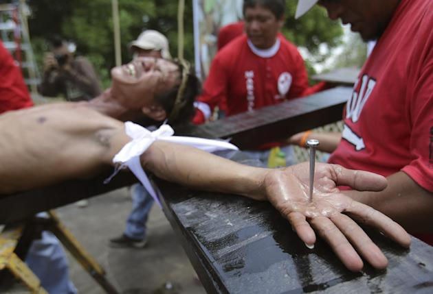 A Filipino devotee grimaces as he is nailed to a cross to re-enact the crucifixion of Jesus Christ in Santa Lucia village, Pampanga province, northern Philippines on Friday, April 18, 2014. Church lea