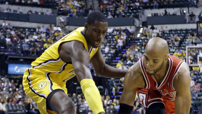 Indiana Pacers center Roy Hibbert, left, attempts to knock the ball away from Chicago Bulls forward Taj Gibson in the first half of an NBA preseason basketball game in Indianapolis, Saturday, Oct. 5, 2013