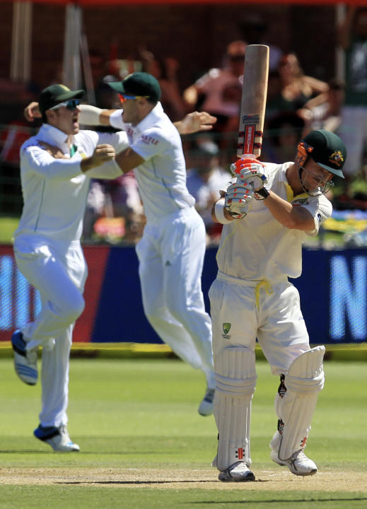 Australia's batsman David Warner, right, reacts as South Africa's captain Graeme Smith, left, and teammate Faf du Plessis, center, celebrate his dismissal on the third day of their second cric
