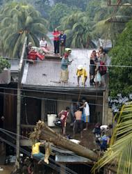 Trapped residents, perched on rooftops, are rescued to safety following a flash flood in Cagayan de Oro city, Philippines, Saturday, Dec. 17, 2011. A tropical storm triggered flash floods in the southern Philippines, killing scores of people and missing more. Mayor Lawrence Cruz of nearby Iligan said the coast guard and other rescuers were scouring the waters off his coastal city for survivors or bodies that may have been swept to the sea by a swollen river. (AP Photo/Froilan Gallardo)