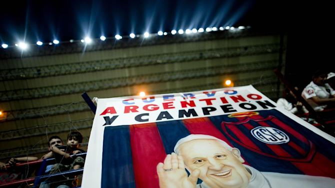 """A banner with an image of Pope Francis and a message that reads in Spanish: """"Cuervo, Argentine and Champion,"""" hangs from the stands during a national soccer league match between San Lorenzo and Colon de Santa Fe in Buenos Aires, Argentina, Saturday, March 15, 2014. The San Lorenzo football club launched a special edition team jersey to mark the first anniversary of Pope Francis's election as pontiff, who is a huge fan. The jersey features an  image of Francis with a message that reads in Spanish; """"Happy anniversary."""""""