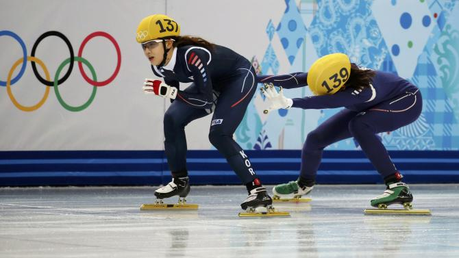 South Korea's Kong Sang-jeong is pushed by teammate Shim Suk-Hee during the women's 3,000 metres short track speed skating semi-finals relay race at the Iceberg Skating Palace during the Sochi 2014 Winter Olympics