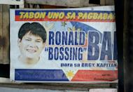 A campaign poster showing an image of Ronaldo Bae, who once ran in local elections for the post of village chief, hanging from a shanty house in Kawit, south of Manila, on January 4, 2013. Bae allegedly went on a rampage and killed five people on Friday, before dying in a gunbattle with police