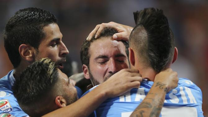 Napoli forward Gonzalo Higuain, second from right, of Argentina, celebrates with his teammates Marek Hamsik, of Slovakia, right, Miguel Britos, top left, and Lorenzo Insigne, left, after scoring during the Serie A soccer match between AC Milan and Napoli at the San Siro stadium in Milan, Italy, Sunday, Sept. 22, 2013