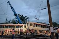 Workers inspect and remove a derailed train carriage in Hong Kong, on May 17, 2013. Over 60 people were injured when a two-car train derailed on Hong Kong's light railway in the north of the city, throwing passengers onto the floor, police said