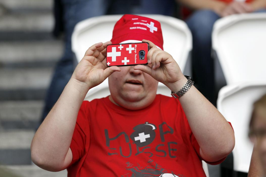 Switzerland fan takes a photograph before the match