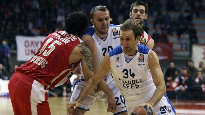 Olympiakos' Georgios Printezis, left, tries to stop Anadolou Efes' Dusko Savanovic, center, as his teammate Dusko Savanovic drives the ball during their Euroleague basketball match of Top 16 in the port of Piraeus, near Athens, Thursday, Feb. 13, 2014. (AP Photo/Thanassis Stavrakis)