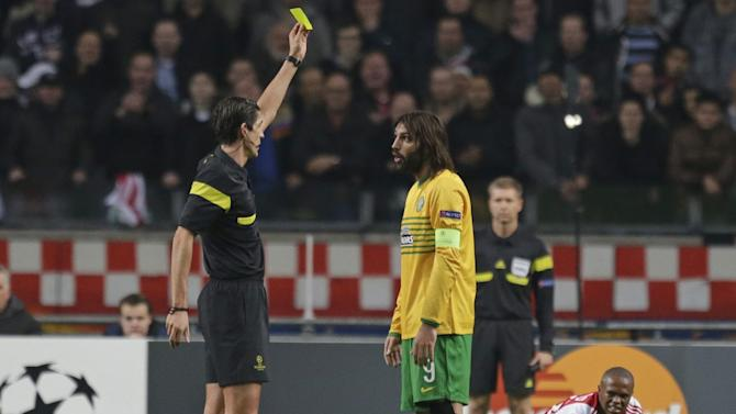 Referee Deniz Aytekin of Germany shows a yellow card to Celtic's Giorgos Samaras, center, after he fouled Ajax's Thulani Serero, rear right, during the Champions League Group H soccer match between Ajax Amsterdam and Celtic Glasgow at ArenA stadium in Amsterdam, Netherlands, Wednesday, Nov. 6, 2013