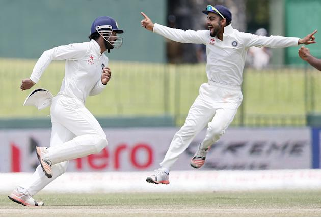 India's Rahul celebrates with captain Kohli after taking the catch to dismiss Sri Lanka's Thirimanne during the final day of their third and final test cricket match  in Colombo