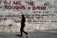 "A woman walks past graffiti outside the Athens Academy on September 20. The ""troika"" of international creditors called time out Friday on lengthy bailout negotiations with the Greek government, deciding on a pause for about a week."