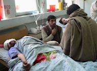 Afghans wounded in the suicide attack receive medical treatment in Jalalabad. A Taliban suicide car bomber targeting NATO troops at an airport in eastern Afghanistan killed nine people Monday, the seventh day of violence over the burning of the Koran at a US airbase