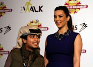 A young Bahraini smiles after having his picture taken with TV star Kim Kardashian, in Riffa, Bahrain, Dec. 1, 2012. Just hours after reality TV star Kim Kardashian gushed about her impressions of Bahrain, riot police fired tear gas to disperse more than 50 hardline Islamic protesters denouncing her presence in the Gulf kingdom. (AP Photo/Hasan Jamali)