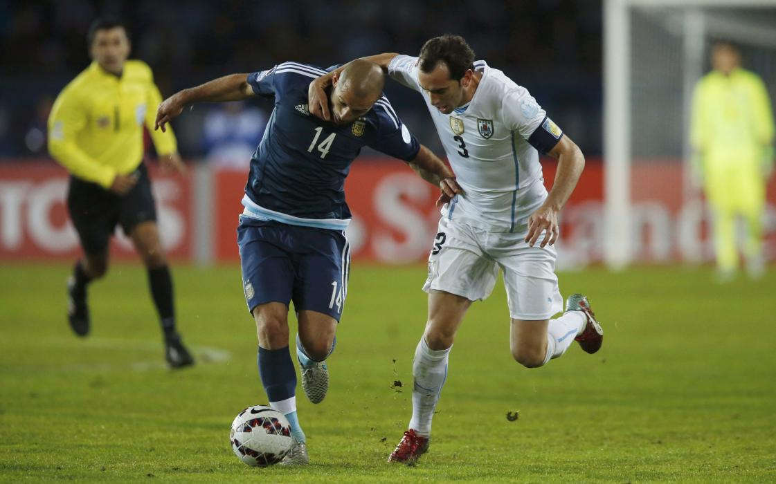 Argentina's Mascherano and Uruguay's Godin fight for the ball during their first round Copa America 2015 soccer match at Estadio La Portada in...