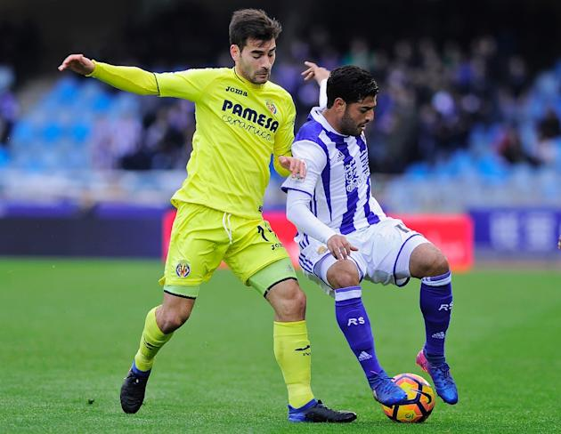 Villarreal's Manuel Trigueros (L) tackles Real Sociedad's Carlos Vela during the Spanish league match at the Anoeta stadium in San Sebastian,  on Februry 19, 2017