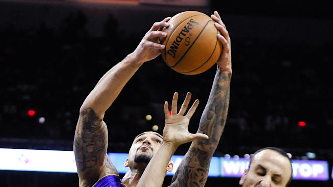 Los Angeles Lakers center Robert Sacre grabs a rebound over San Antonio Spurs guards Cory Joseph, left, and Manu Ginobili of Argentina during the second half of an NBA basketball game Friday, March 14, 2014, in San Antonio. (AP Photo/Bahram Mark Sobhani)