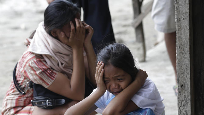 Relatives cry upon seeing the remains of their relative at a damaged public market which serves as a makeshift mortuary for typhoon's Bopha's victims at New Bataan township, Compostela Valley in southern Philippines Saturday Dec. 8, 2012. Search and rescue operations following a typhoon that killed nearly 600 people in the southern Philippines have been hampered in part because many residents of this ravaged farming community are too stunned to assist recovery efforts, an official said Saturday. (AP Photo/Bullit Marquez)